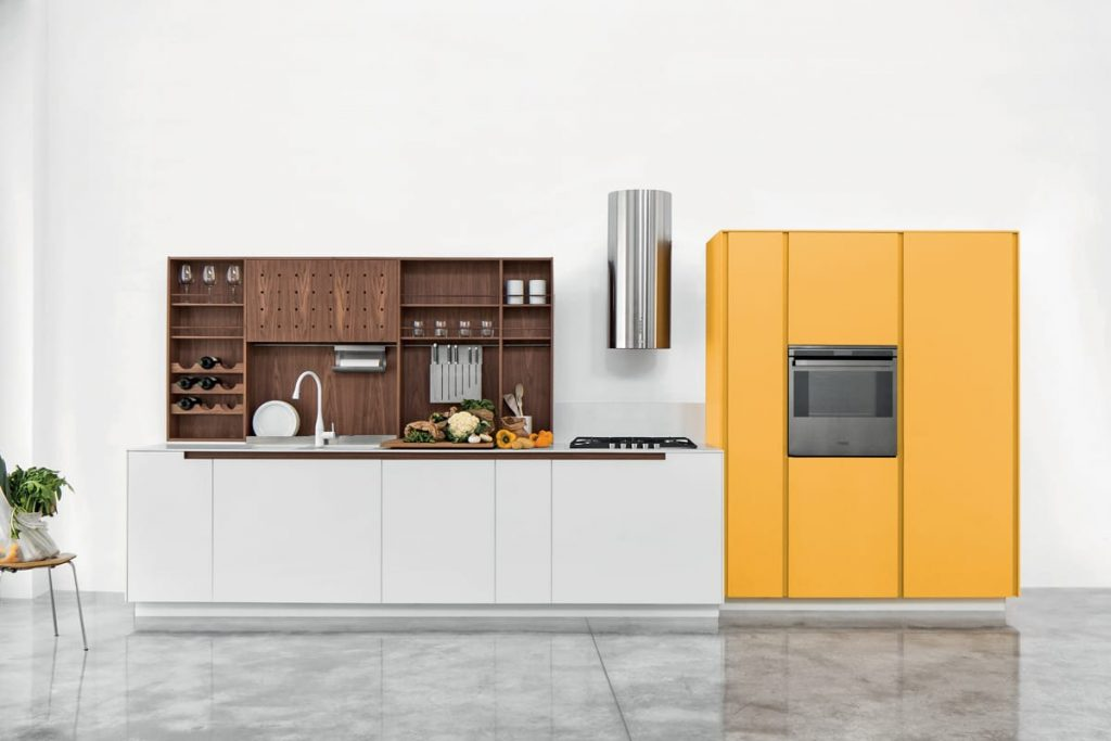 Cucina moderna lineare con elementi a giorno in noce canaletto e ante laccato opaco giallo zafferano.