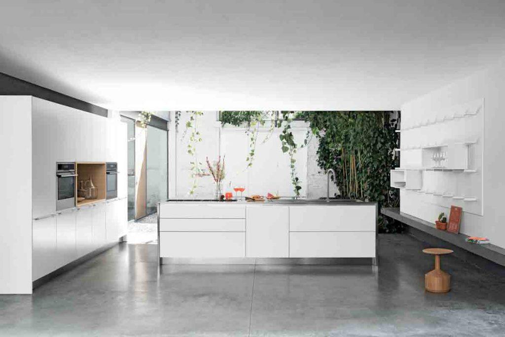 Cucina con isola con ante e piano in fenix. Una grande isola operativa in cui trovano spazio il lavello, il piano cottura e i capienti vani contenitori.