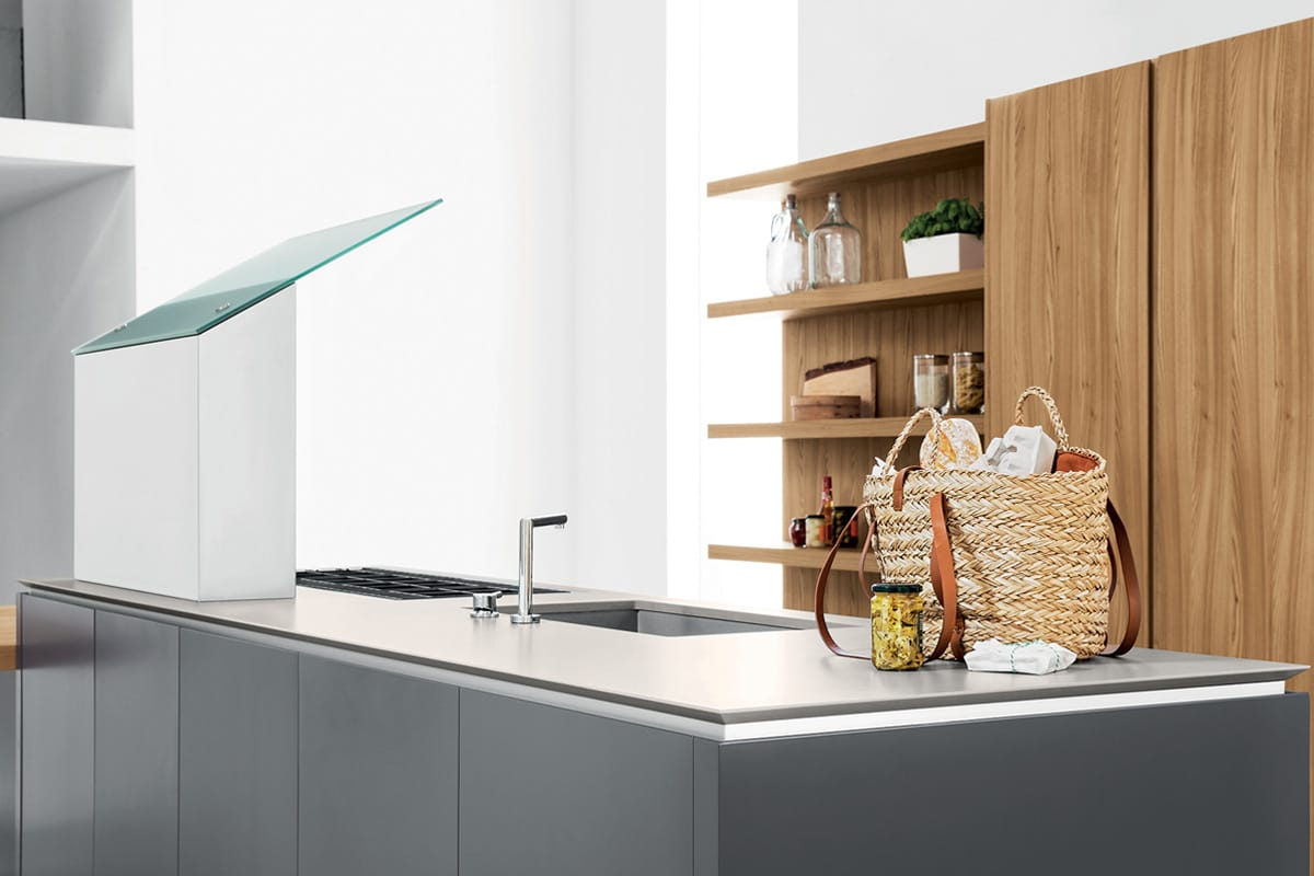 Cucina moderna con isola, colonne attrezzate e boiserie con mensole e vani a giorno.